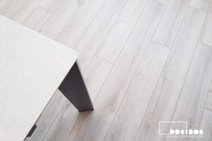 Detalle del suelo parquet sintético gris en el comedor, donde se ve la pata negra de una mesa porcelánica.