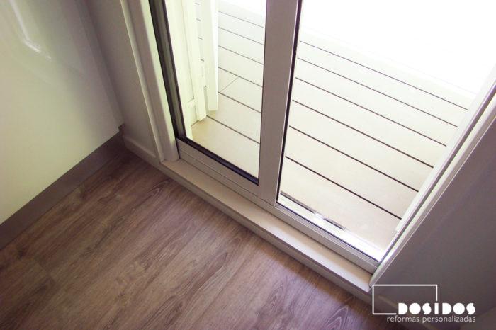 Puerta de aluminio corredera interior salida a la terraza. Suelo parquet sintético y suelo técnico de terraza.