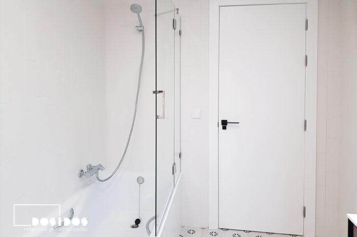 Cuarto de baño blanco con bañera, mampara de cristal abatible y puerta lisa lacada en blanco con la manivela negra