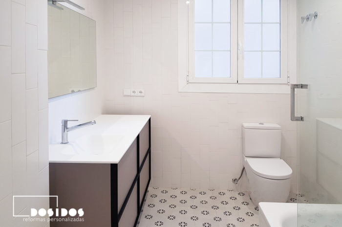 Reforma del cuarto de baño vintage, azulejos blanco mate, suelo con dibujos y mueble en color beige y negro
