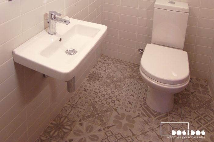 Baño pequeño con un lavabo de porcelana pequeño suspendido, inodoro y azulejos grises con dibujos en el suelo de vives cerámica.