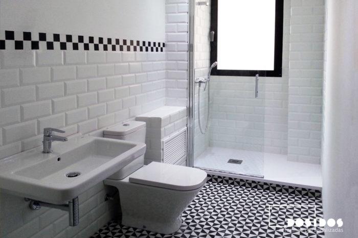 Baño vintage con azulejos blancos biselados y suelo negro con dibujos. Inodoro, lavabo y ducha blancos.