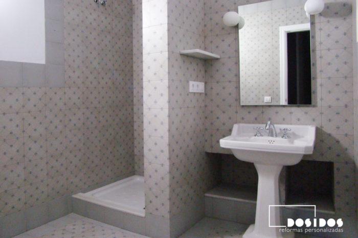 Reforma de baño con lavabo de porcelana retro y grifo bimando vintage cromado. Azulejo de vives cerámica gris dibujo.