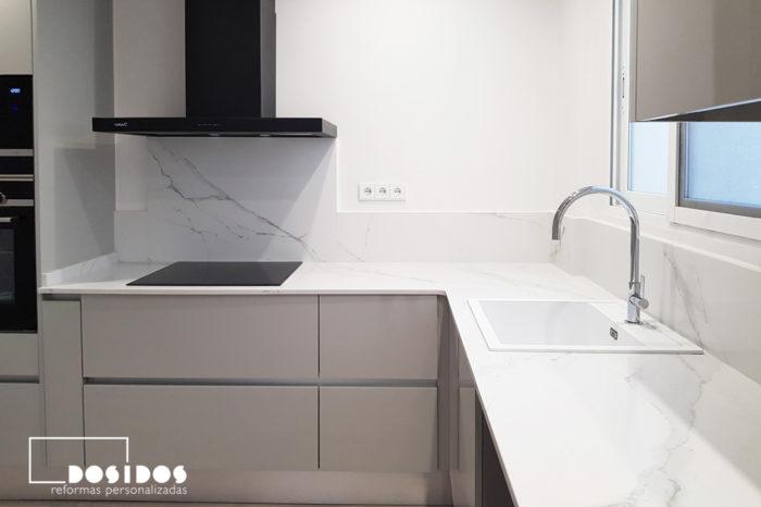 Cocina en forma de L con muebles grises, encimera de cocina blanca y campana extractora decorativa negra.