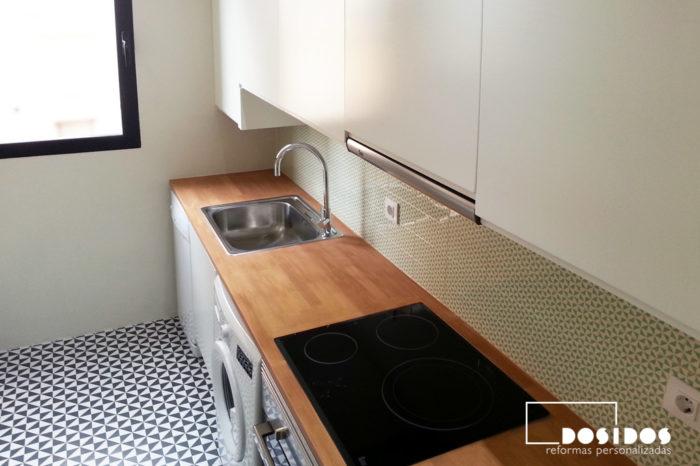 cocina pequeña estilo vintage con encimeras de madera, frente con azulejos verdes con dibujo y muebles blancos