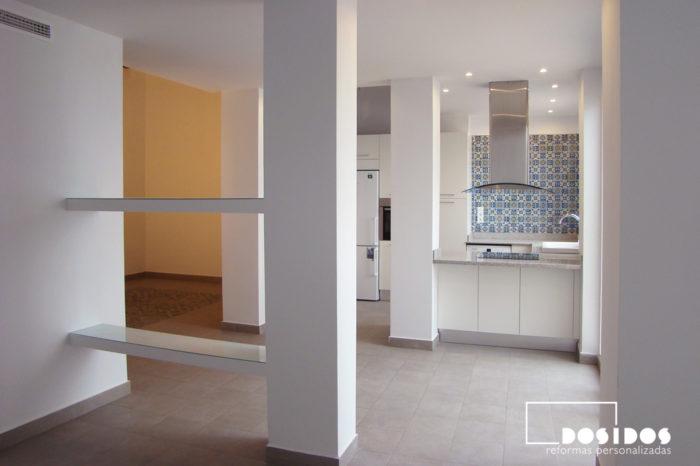 Reforma de una cocina blanca abierta al salón con barra, separando el ambiente unas estanterías de escayola.