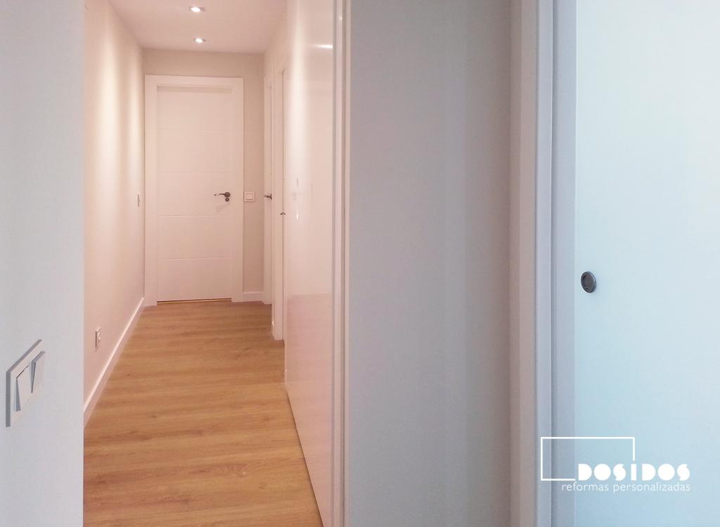 Reforma de una vivienda, detalle del pasillo con parquet. paredes pintada en color claro y puerta de entrada a la cocina corredera de vidrio mate.