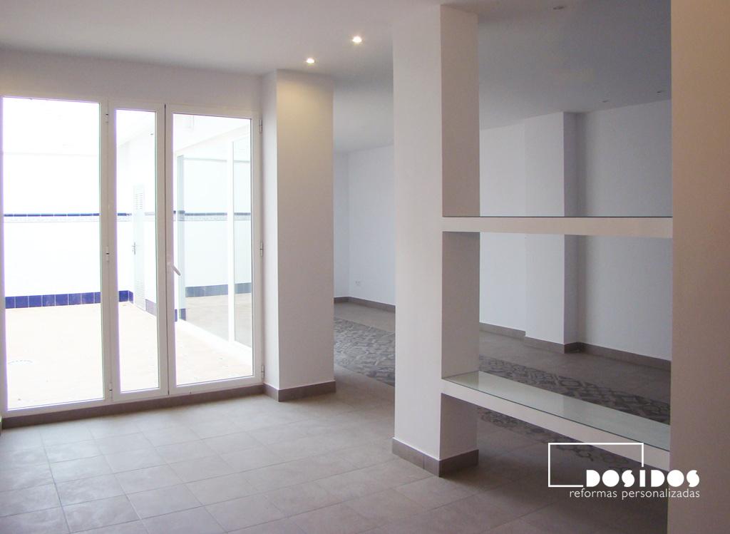Salón abierto a la cocina con separación de estancias usando estanterías de escayola y cristal, con salida y vista a la terraza.