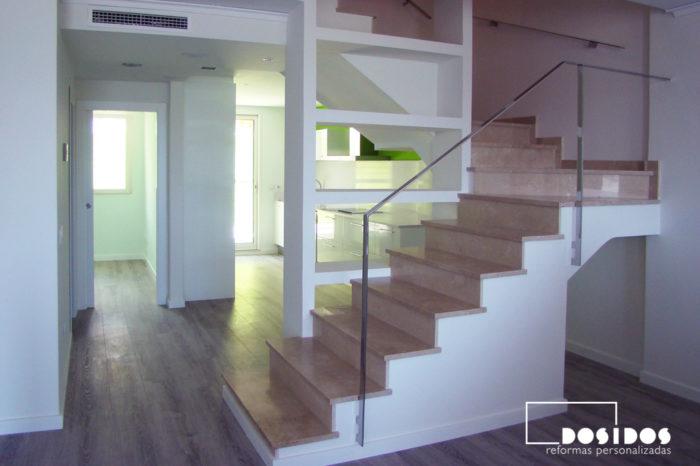 Reforma de unifamiliar diáfana, salón y cocina abierta separados por escalera barandilla inox y estantes de escayola.