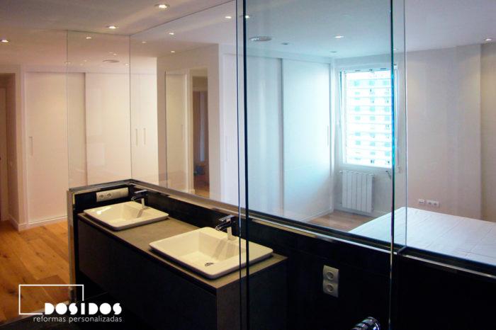 Separación de cristal entre el baño habitación suite con dos lavabos y vestidor