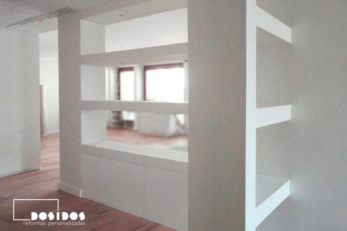 Separación entre al salón y el recibidor con estanterías de pladur blancas
