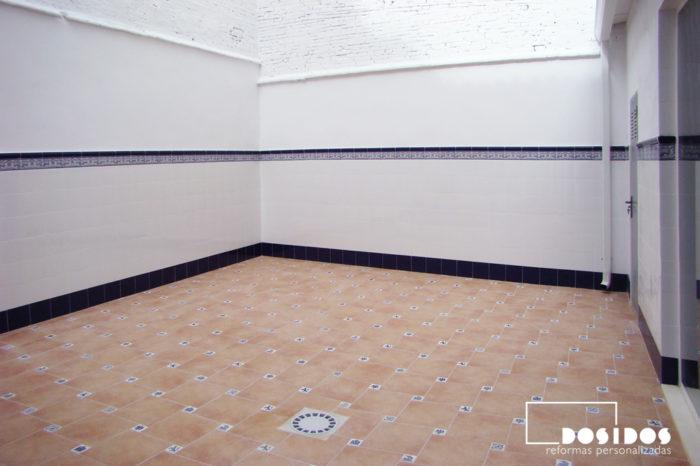 Terraza con zocalada de azulejo Valenciano alicatado a media altura en color blanco con cenefa dibujos azules.