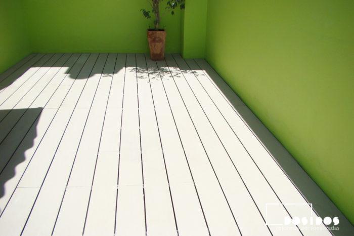 Terraza con suelo técnico y parades pintadas en verde.