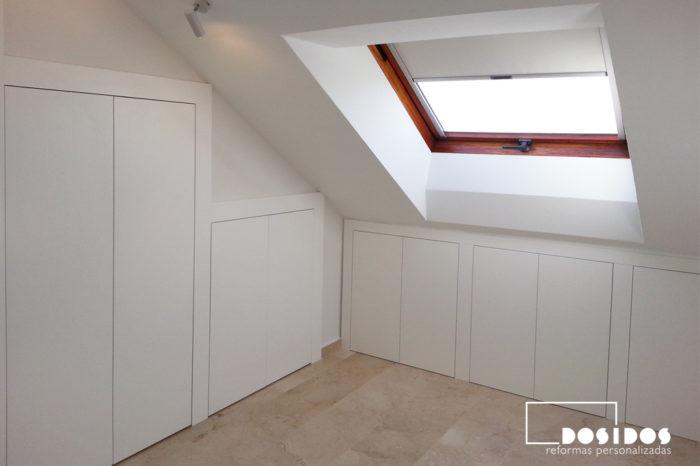 Armarios blancos en una habitación en una buhardilla para aprovechamiento de huecos. Ventana con screen para el sol.