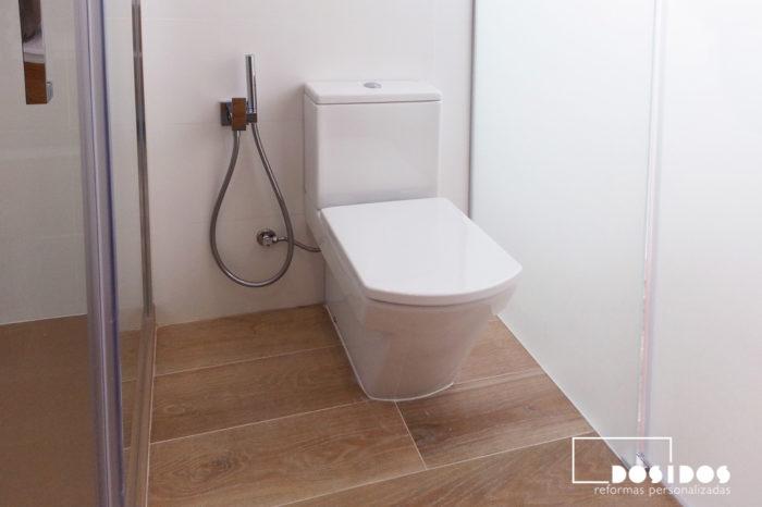 Baño blanco con suelo azulejo madera, inodoro junto al grifo bidé wc.
