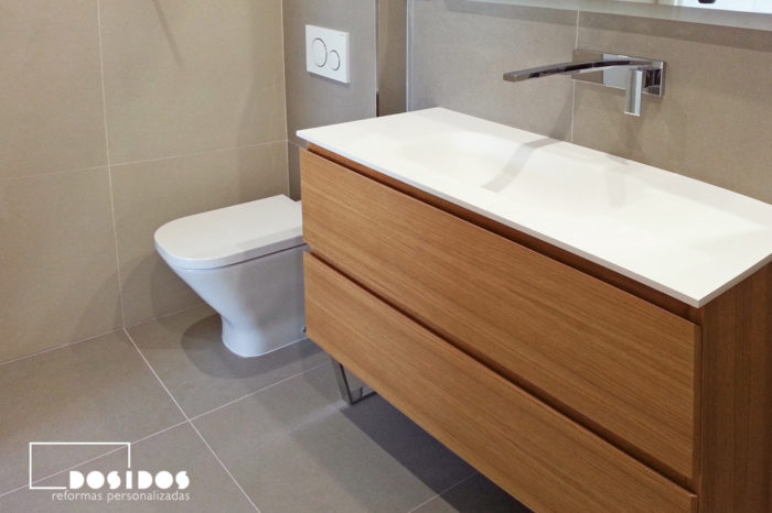 Baño moderno, inodoro con cisterna empotrada y mueble de madera natural.