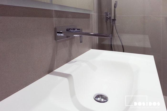 Detalle del mueble de baño con lavabo de krion y grifo empotrado a pared.
