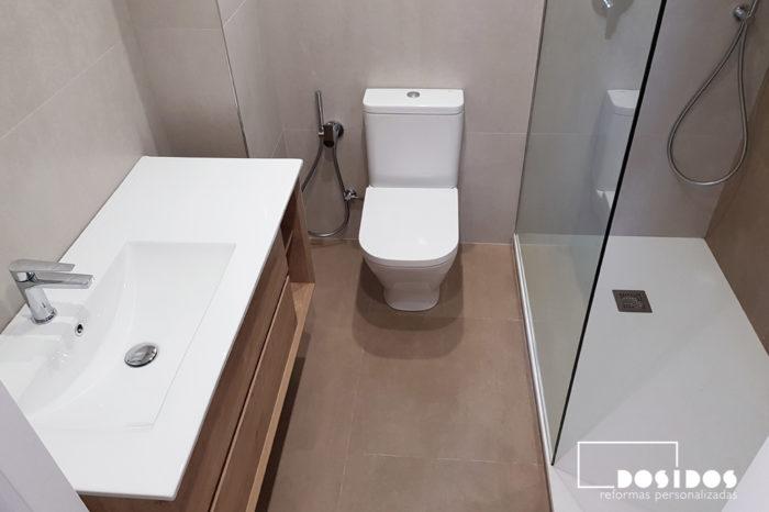 Baño con mueble de madera lavabo descentrado, inodoro con grifo de bidé wc y ducha con fijo de cristal
