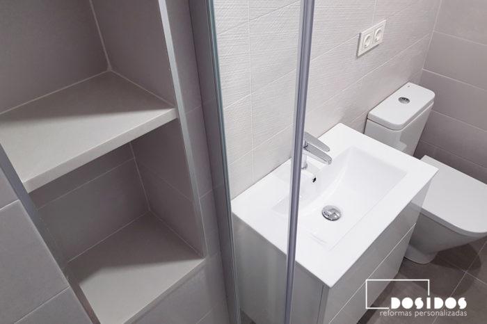 Baño pequeño vista de los estantes de la hornacina dentro la ducha