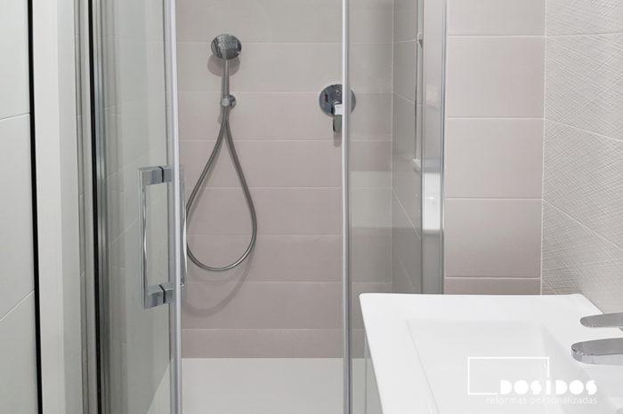 Ducha de una baño pequeño con mampara de fijo y puerta abatible