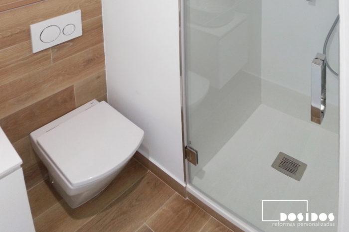 Un baño pequeño, detalle del inodoro empotrado y plato de ducha.