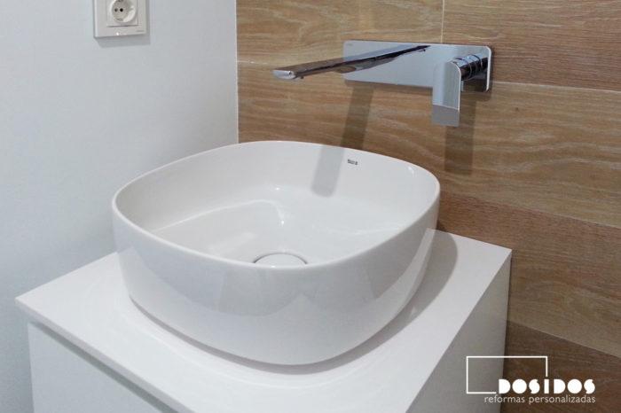 Detalle del lavabo de porcelana sobre un mueble y grifo a pared en un baño pequeño.