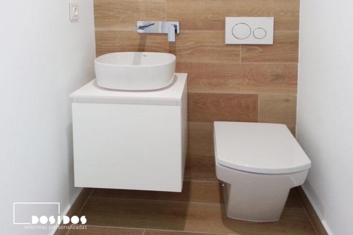 Un baño pequeño, detalle del lavabo sobre un mueble, grifo a pared e inodoro empotrado.