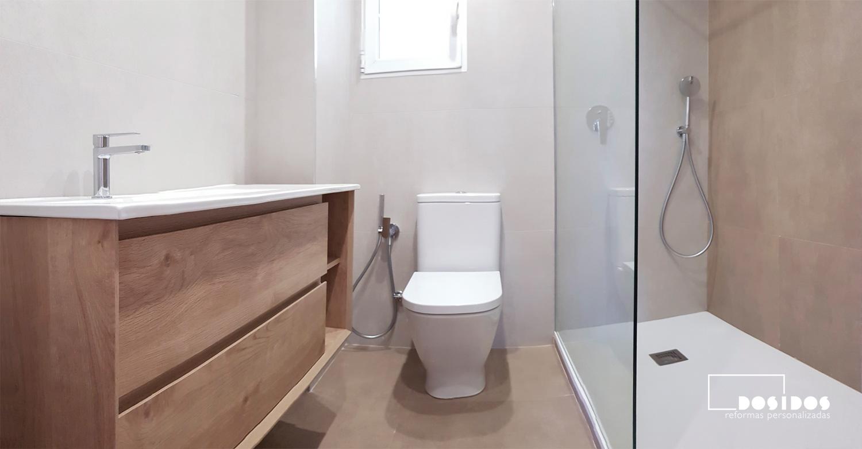 Reforma de un baño en suite con mueble de madera con uñero e inodoro con grifo de bidé wc y ducha con fijo de cristal