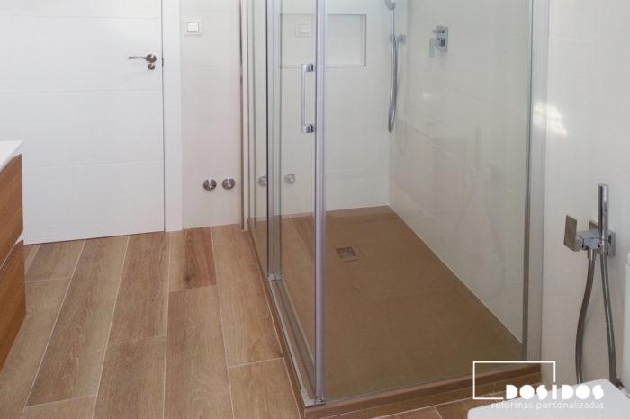 Baño blanco con suelo de azulejo imitación madera y plato de ducha marrón igualando el color del suelo.