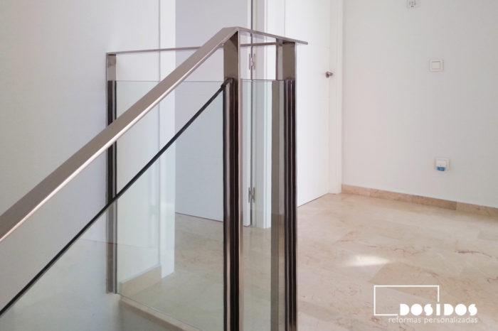 Detalle de una barandilla de escalera, fabricada a medida en pletina de acero inoxidable y cristal transparente.