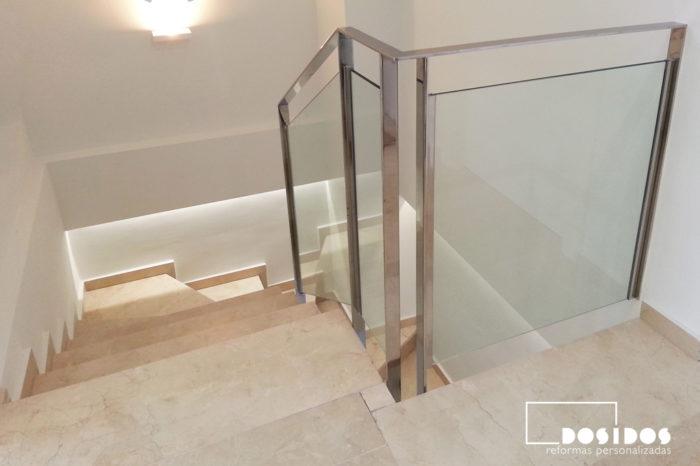 Barandilla de escalera fabricada en pletina de acero inoxidable y cristal transparente.