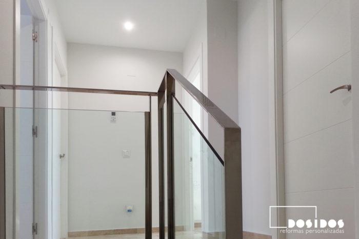 Detalle de la barandilla de escalera de pletina de acero y cristal en el distribuidor entrada a la habitaciones.