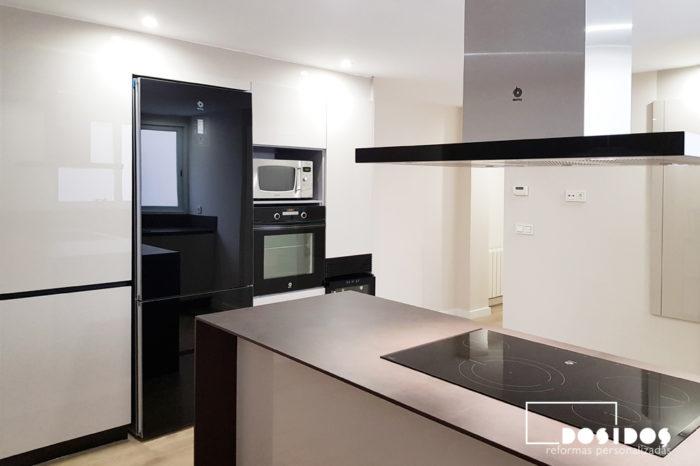 Cocina abierta detalle de los muebles en columna beige con electrodomésticos de cristal negro y encimera dekton