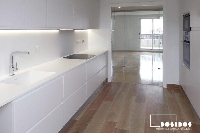 Muebles de cocina con gran almacenamiento, encimera y paredes de color blanco y suelo de azulejos imitación a madera.