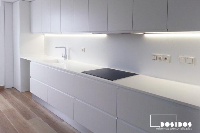 Cocina lineal, con muebles y encimera de Krion en color blanco, iluminación tira led bajo los muebles altos.
