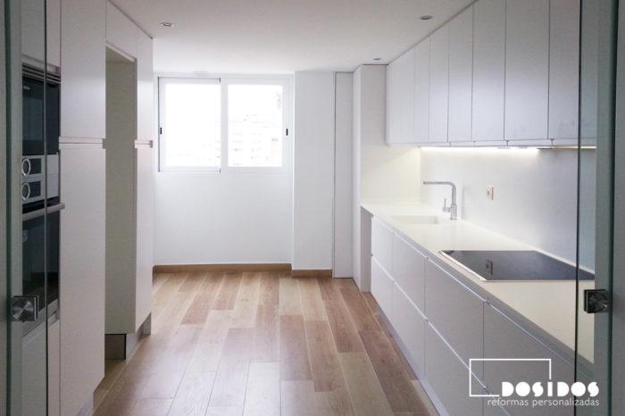 Reforma de una cocina lineal dos bancadas con muebles, encimera de Krion y pintura en color blanco y el suelo azulejo imitación madera.