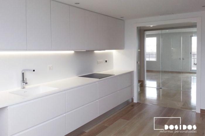 Una cocina banca, encimera de Krion y el pavimento azulejo imitación madera. Entrada con puerta de cristal transparente.