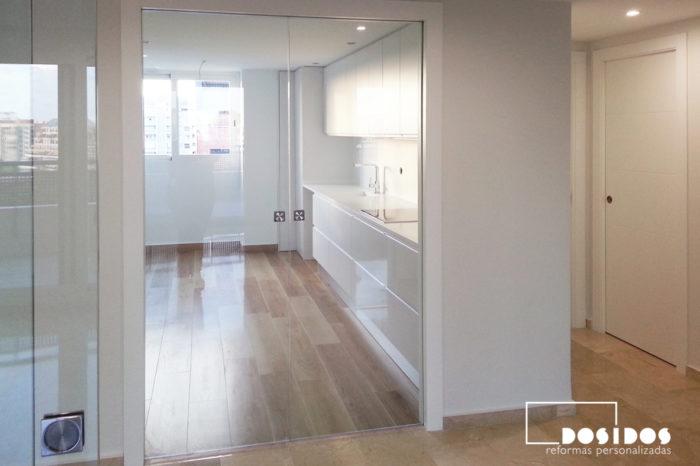 Entrada de una cocina con puerta corredera interior de dos hojas de cristal transparente.
