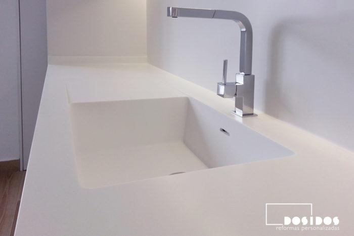 Encimera y frente de cocina de krion blanco con el fregadero integrado y el grifo cromado de diseño cuadrado extraible.
