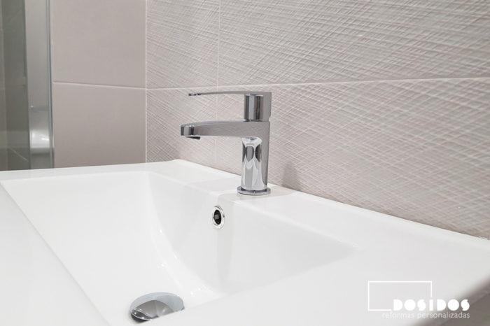 Un lavabo de porcelana blanca con su grifo, en un baño pequeño con azulejos plata líneas con relieve