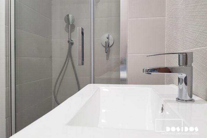 Ducha de un baño pequeño con mampara de fijo y puerta y detalle del grifo y lavabo