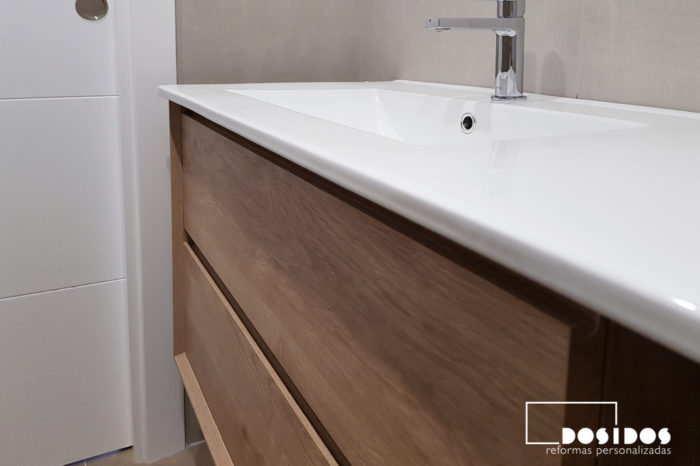 Detalle del mueble de baño de madera dos cajones y lavabo descentrado