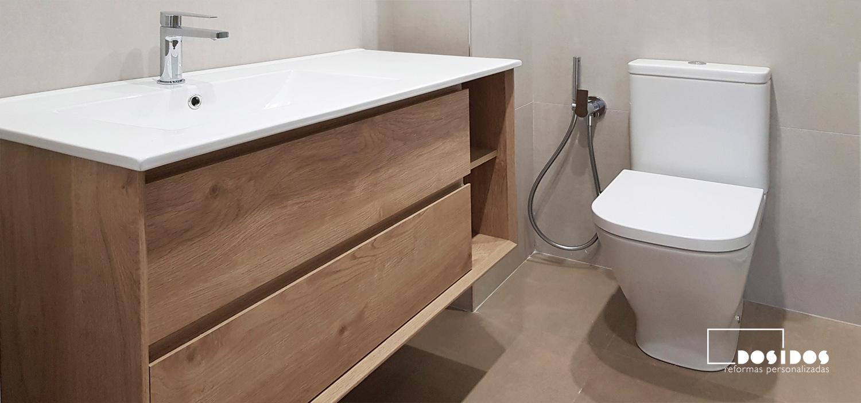 Baño detalle del mueble de madera lavabo descentrado e inodoro con grifo de bidé wc