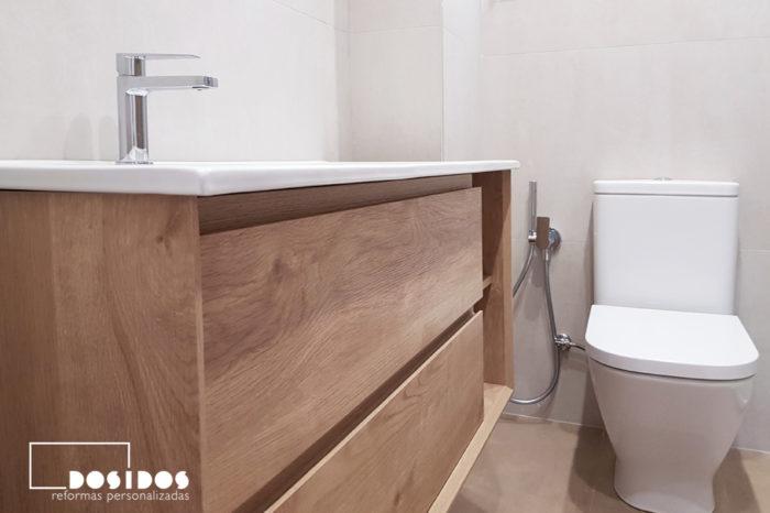 Reforma de un baño detalle del mueble de madera con uñero e inodoro con grifo de bidé wc