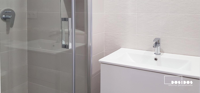 Mueble blanco con lavabo de porcelana fondo reducido en un baño pequeño con ducha