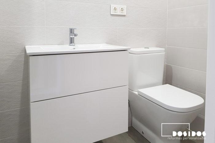 Mueble blanco con lavabo de porcelana fondo reducido e inodoro compacto para un baño pequeño
