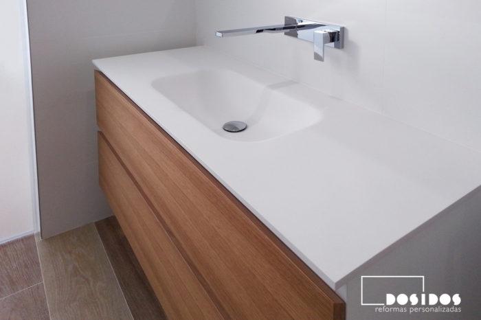 Mueble de baño con 2 cajones de madera y laterales lacados en blanco, un lavabo de krion con grifo empotrado a pared.