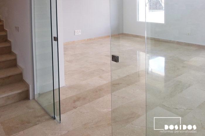 Salón grande con puerta doble de cristal transparente corredera y dos fijos laterales.