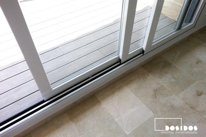 Puerta de aluminio, corredera con rotura de puente térmico en color blanco y gris para salida a la terraza con suelo técnico.