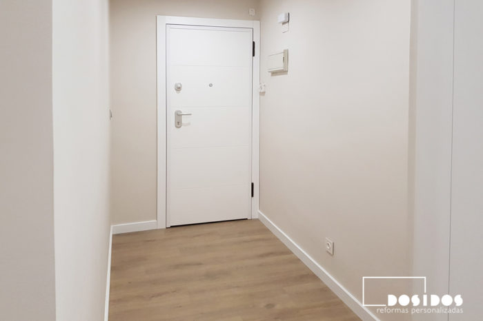 Recibidor de una vivienda con puerta blindada interior blanca